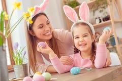 Matka i córka w królików ucho Easter świętowaniu siedzi dziewczyna grymas wpólnie w domu Obraz Royalty Free