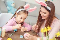 Matka i córka w królików ucho Easter świętowaniu siedzi dziewczyna obrazu obrazek na jajku koncentrującym wpólnie w domu Zdjęcie Stock