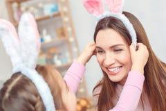 Matka i córka w królików ucho Easter świętowaniu siedzi dziewczyny kładzenia bazel na mamy ` s głowy zakończeniu wpólnie w domu Zdjęcia Stock