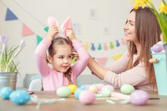 Matka i córka w królików ucho Easter świętowaniu siedzi dziewczyny wzruszającego bazel wpólnie w domu Obraz Royalty Free
