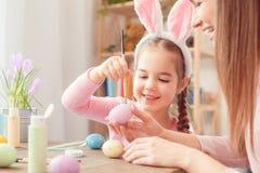 Matka i córka w królików ucho Easter świętowaniu siedzi obraz kropki na jajku wpólnie w domu Obrazy Royalty Free