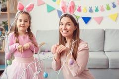 Matka i córka w królików ucho Easter pojęciu pozuje jak króliki wpólnie w domu zdjęcia stock