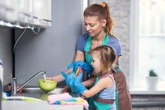 Matka i córka w kuchennych domycie naczyniach w domu fotografia stock