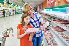 Matka i córka wybieramy mięso w sklepie Fotografia Royalty Free
