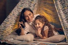 Matka i c?rka siedzimy w teepee namiocie, czytelnicze opowie?ci z latark? szcz??liwa rodzina fotografia stock