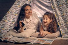 Matka i c?rka siedzimy w teepee namiocie, czytelnicze opowie?ci z latark? szcz??liwa rodzina obrazy stock