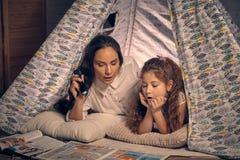 Matka i c?rka siedzimy w teepee namiocie, czytelnicze opowie?ci z latark? szcz??liwa rodzina obraz stock