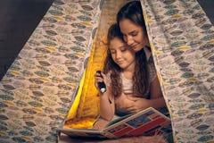 Matka i c?rka siedzimy w teepee namiocie, czytelnicze opowie?ci z latark? szcz??liwa rodzina zdjęcie stock