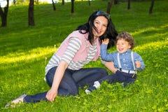 Matka i chłopiec ma zabawę w trawie Zdjęcia Royalty Free