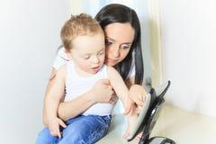 Matka i chłopiec używa cyfrową pastylkę wewnątrz Fotografia Stock
