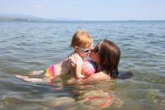 Matka i córka bawić się w morzu Zdjęcia Stock