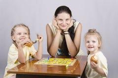 Matka i dwa córki bawić się grę planszowa fotografia stock