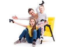 Matka i dwa córki bawić się gry z joystickiem Fotografia Stock