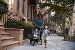 Matka i dwa córki bierze spaceru puszkowi ulicę zdjęcia royalty free