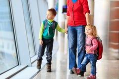 Matka i dwa dzieciaka chodzi w lotnisku fotografia royalty free