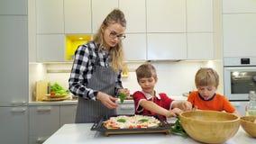 Matka i dwa dzieciaka robi pizzy z basilem zbiory