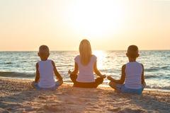 Matka i dzieci ćwiczenia na plaży, one spotykamy wschód słońca Sprawność fizyczna, sport, joga i zdrowy stylu życia pojęcie, zdjęcie stock