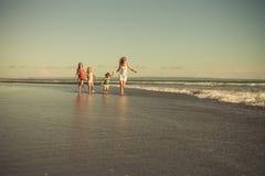 Matka i dzieci biega na plaży Zdjęcia Stock