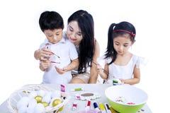 Matka i dzieci maluje Easter jajka obrazy royalty free