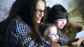 Matka i dzieci z pastylka komputerem ogląda w domu kreskówki i bawić się zbiory wideo