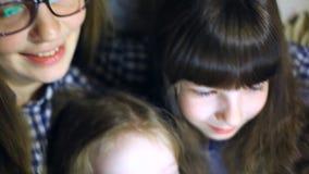 Matka i dzieci z pastylka komputerem ogląda w domu kreskówki i bawić się zdjęcie wideo