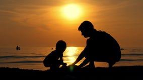 Matka i dziecko bawić się z piaskiem na dennym brzeg przeciw zmierzchowi zbiory