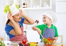 Matka i dziecko ma zabawę w kuchni bawić się z warzywami a Zdjęcia Stock