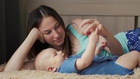 Matka i dziecko na białym łóżku Mama i chłopiec w pieluszce bawić się w pogodnej sypialni Rodzic i małe dziecko relaksuje przy zbiory wideo