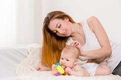 Matka i dziecko na białym łóżku Mama i dziewczynka w pieluszce bawić się w pogodnej sypialni Zdjęcia Stock