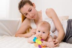 Matka i dziecko na białym łóżku Mama i dziewczynka w pieluszce bawić się w pogodnej sypialni Zdjęcie Stock