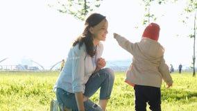 Matka i dziecko obwąchujemy rośliny Szczęśliwy Młody Rodzinny odprowadzenie W parku zdjęcia royalty free