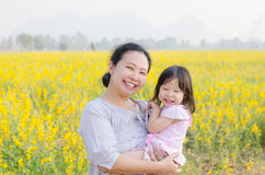 Matka i dziecko ono uśmiecha się w kwiatu polu Zdjęcia Royalty Free