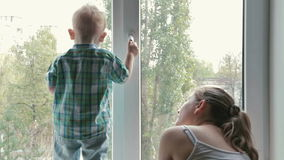 Matka i dziecko przyglądający out okno zdjęcie wideo