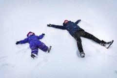 Matka i dziecko robi aniołom w śniegu zdjęcie stock