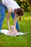 Matka i dziecko robi ćwiczenie rutynie outdoors Zdjęcia Royalty Free