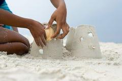 Matka i dziecko stawia skorupę na sandcastle Fotografia Stock