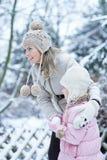 Matka i dziecko tworzy snowball w zimie Obrazy Stock