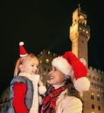 Matka i dziecko w Bożenarodzeniowych kapeluszach patrzeje each inny, Włochy Fotografia Royalty Free