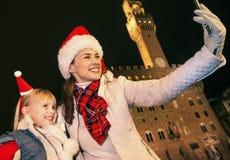 Matka i dziecko w Bożenarodzeniowych kapeluszach bierze selfie w Florencja Zdjęcia Stock