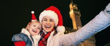 Matka i dziecko w Bożenarodzeniowych kapeluszach w Florencja bierze selfie Zdjęcia Stock