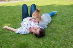 Matka i dziewczyna na trawie, dziewczyny s głowa na matki klatce piersiowej obraz stock