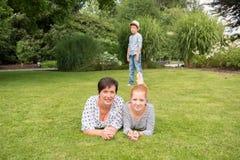 Matka i dziewczyna na trawie, mała chłopiec w tle fotografia stock