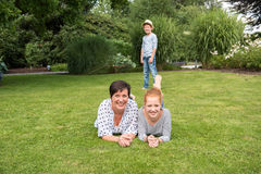 Matka i dziewczyna na trawie, mała chłopiec w tle fotografia royalty free