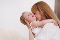 Matka i jej śliczna mała dziewczynka ma zabawę na kanapie przy h Zdjęcia Royalty Free