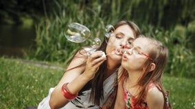 Matka i mała dziewczynka dmucha mydlanych bąble w parku Fotografia Stock