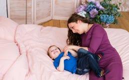 Matka i syn bawić się w sypialni Fotografia Royalty Free
