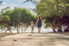 Matka i syn iść denna plaża Kurortu wakacje na tropikalnej plaży ścieżka plażowa zdjęcia stock