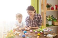 Matka i syn maluje Wielkanocnych jajka Szczęśliwa rodzinna mama i dziecko syn malujemy Easter jajka z kolorami Przygotowanie dla  zdjęcia stock
