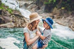Matka i syn relaksuje pod siklawą piękni pojęcia basenu wakacje kobiety potomstwa Fotografia Stock