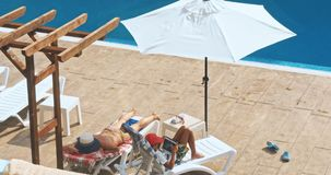Matka i syn relaksuje przy sunbed blisko basenu przy kurortem zdjęcie wideo